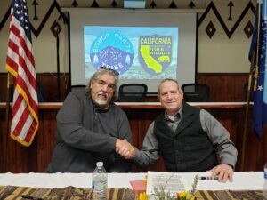 Member of the Bishop Paiute Tribe and CDFW staff shake hands after signing MOU